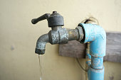 A photo of Chrome faucet and water pipeline with blue pvc pipe, close up