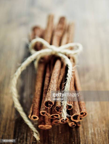 Close up of cinnamon sticks tied with bow of twine on table