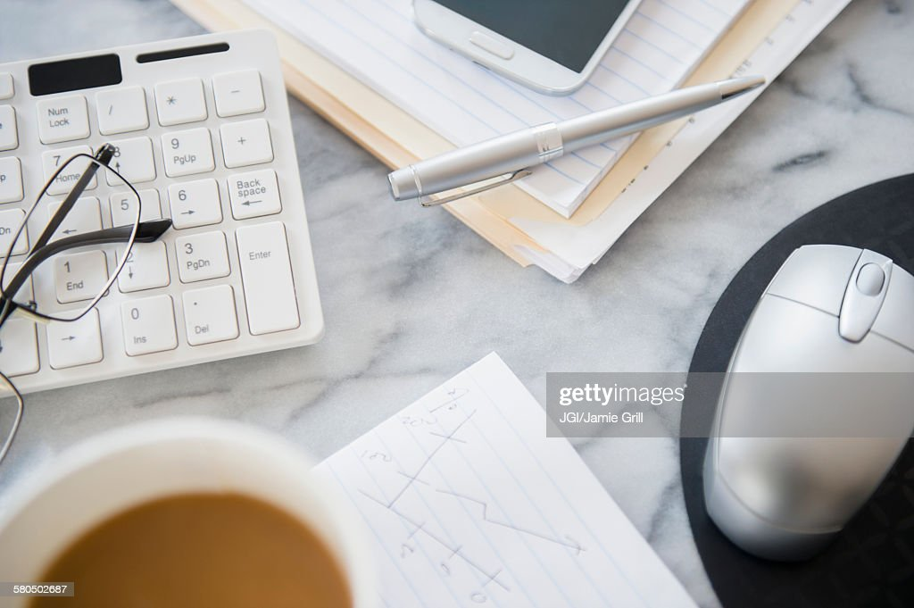 Close up of computer equipment, files and coffee on office desk : Stock Photo