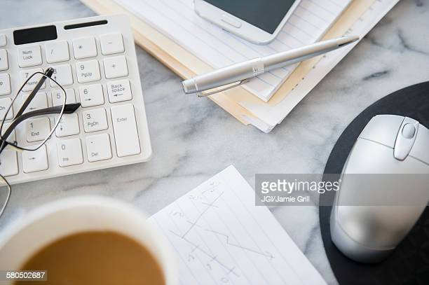 Close up of computer equipment, files and coffee on office desk