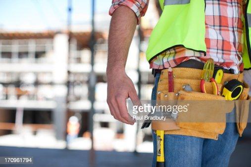 Gros plan de construction travailleur est doté d'une ceinture à outils sur le site de construction