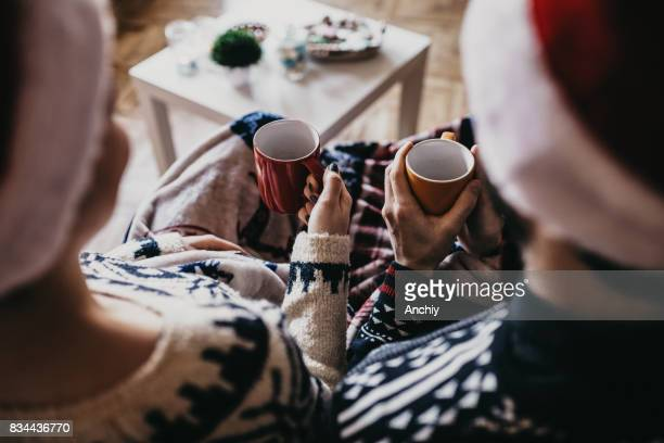 Close up of couple holding mugs with coffee, wearing Santa's hat