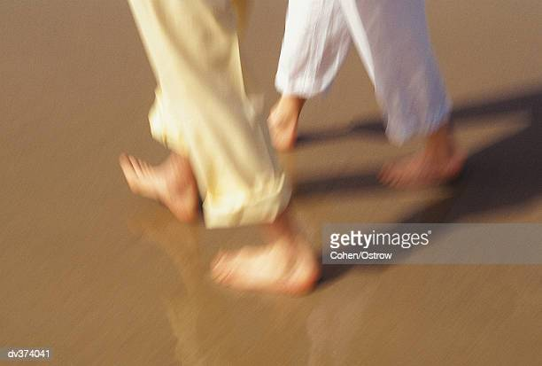 Close up of couples legs walking on beach
