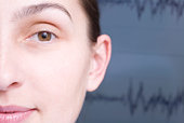 Close up of cropped woman face, sound wave graph in background