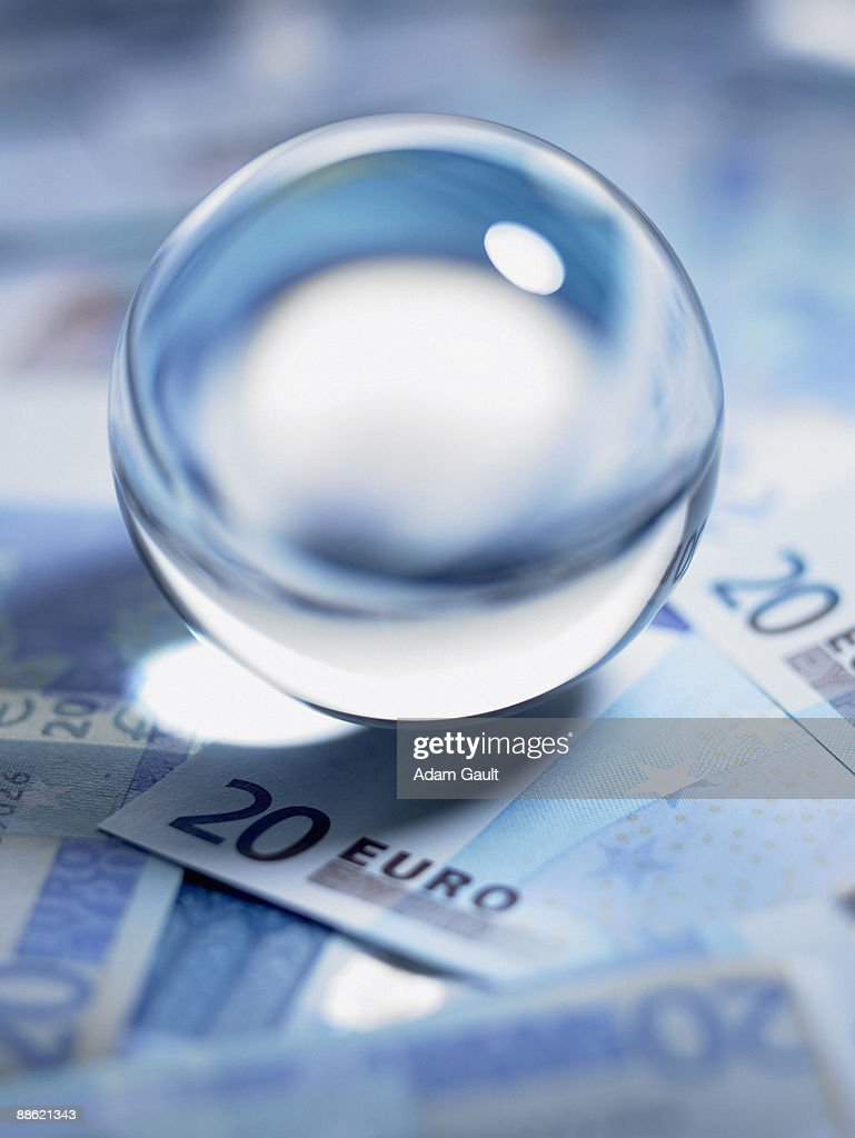 Close up of crystal ball on 20 euro notes