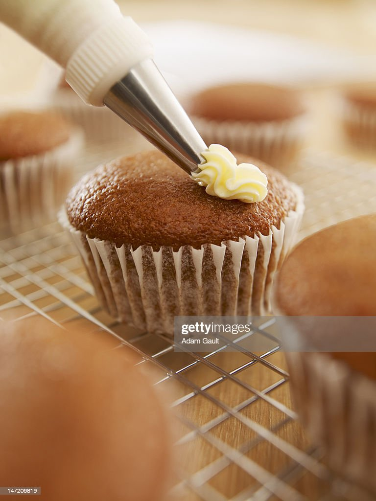 Close up of cupcake being frosted : Stock Photo