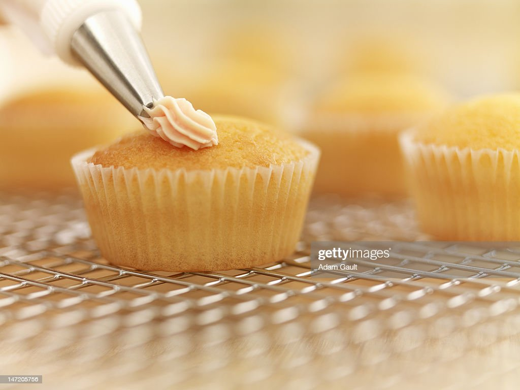 Close up of cupcakes being frosted : Stock Photo