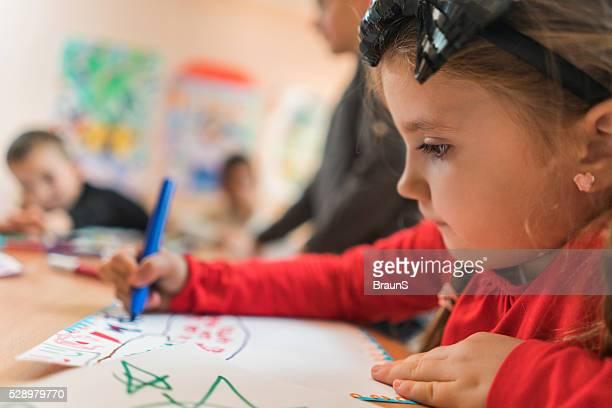 Close up of cute girl drawing in a preschool.