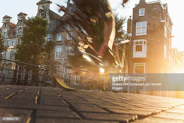 Close up of cyclist riding through cobbled street, Amsterdam, Netherlands