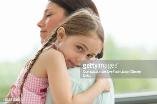 Close up of daughter hugging mother : Stock Photo