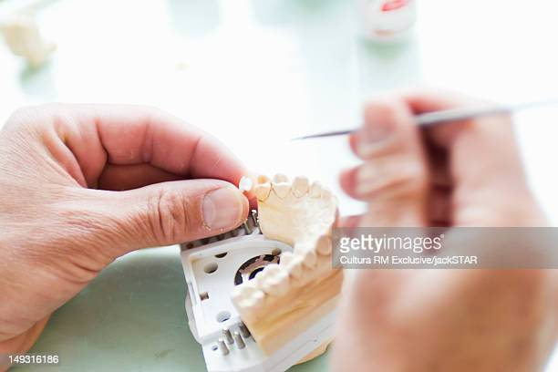 Close up of dentist working on dentures
