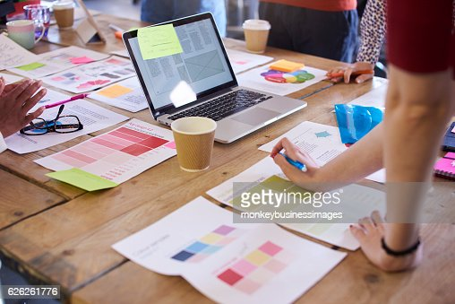 Close Up Of Designers Discussing Layouts And Color Schemes : Stock Photo
