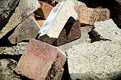 Close up image of discarded cement bricks and pavers in pile outside in sunshine.