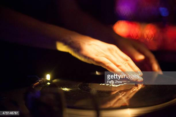 Close up of DJ's hands spinning vinyl in nightclub