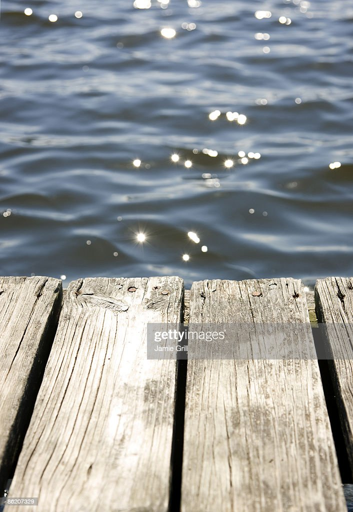 Close up of dock and sun reflecting on lake