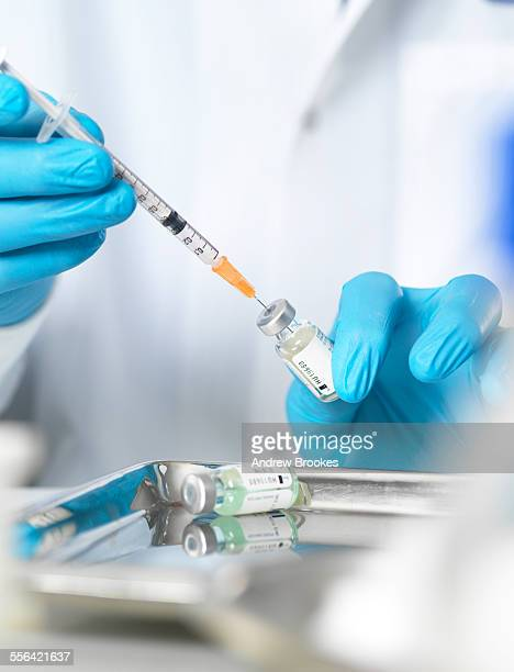 Close up of doctors hands preparing a vaccine to inject patient