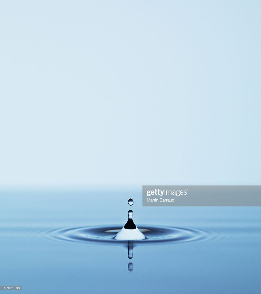 Close up of droplet falling in pool of water : Stock Photo