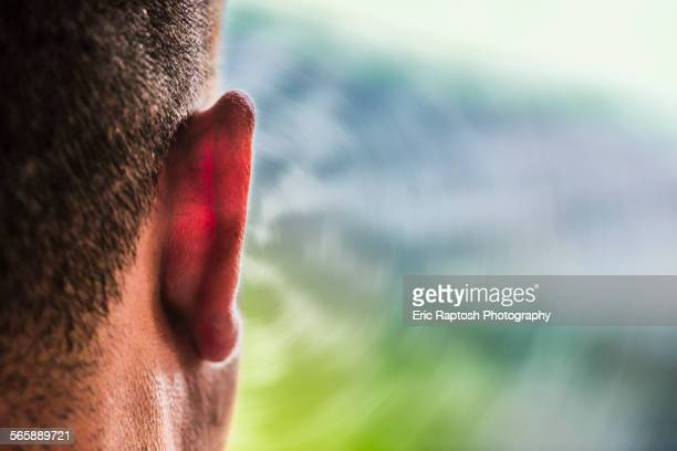 Close up of ear of Caucasian man and sound waves