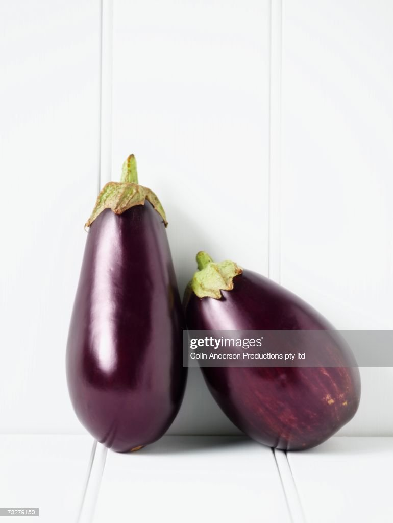 Close up of eggplants leaning against wall : Stock Photo