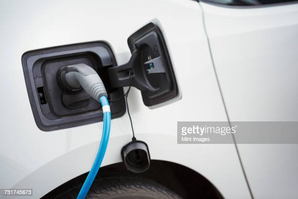 Close up of electric car being charged by a blue cable plugged in, topping up the battery.