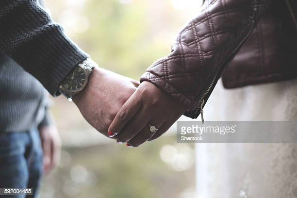 Close up of engaged couple holding hands