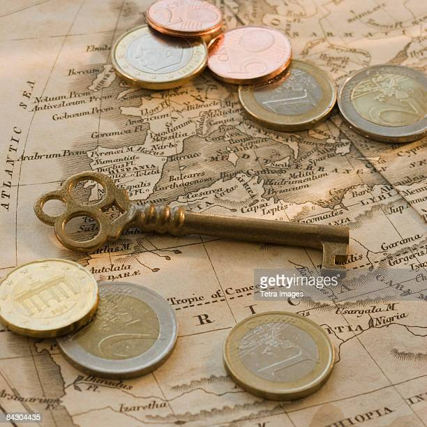 Close up of euro coins, map and antique key