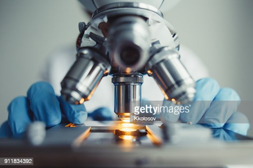 Close up of examining of test sample under the microscope : Stock Photo