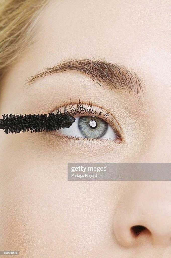 Close up of eye with mascara brush : Stock Photo