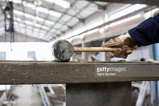 Close up of factory workers hand with rubber hammer in concrete reinforcement factory