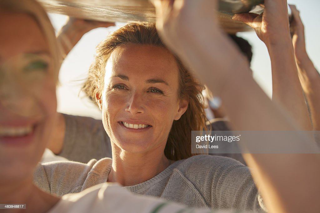 Close up of family carrying surfboard on beach : Stock Photo