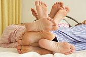 Close Up Of Family's Feet Relaxing On Bed At Home