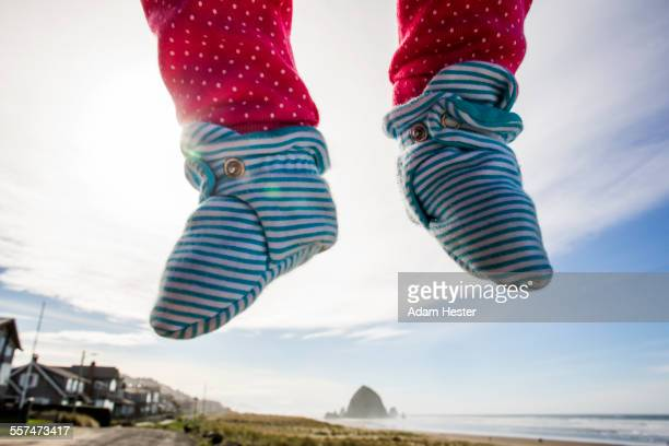 Close up of feet of Caucasian baby hovering over beach