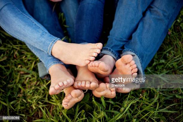 Close up of feet of friends in grass