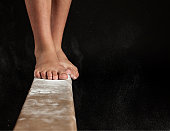 Close up of feet on balance beam covered in chalk
