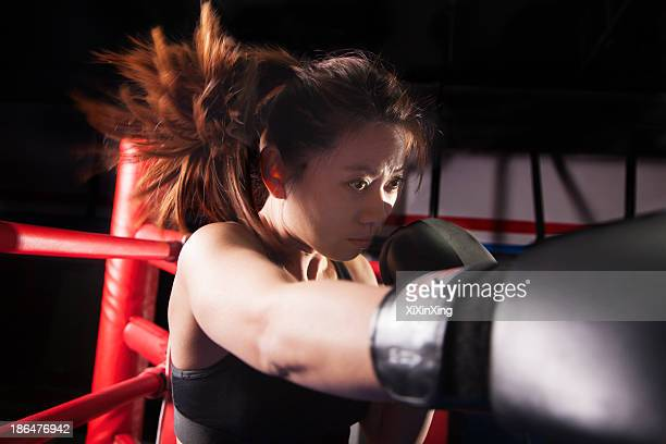 Close up of female boxer throwing a punch, hair in motion