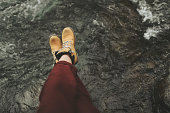 Close up of womans legs in touristic boots sitting on the river bank