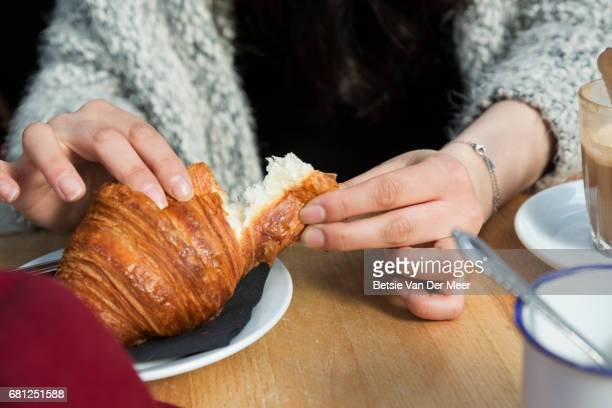 Close up of female hands breaking off a piece of croissant in cafe.