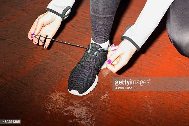 close up of female hands lacing trainers