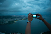 Close up of female hands photographing view of Rio De Janeiro at night, Brazil
