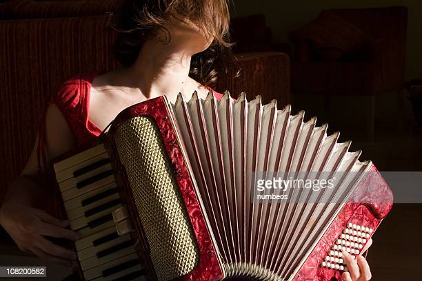 Close up of female playing red vintage accordion