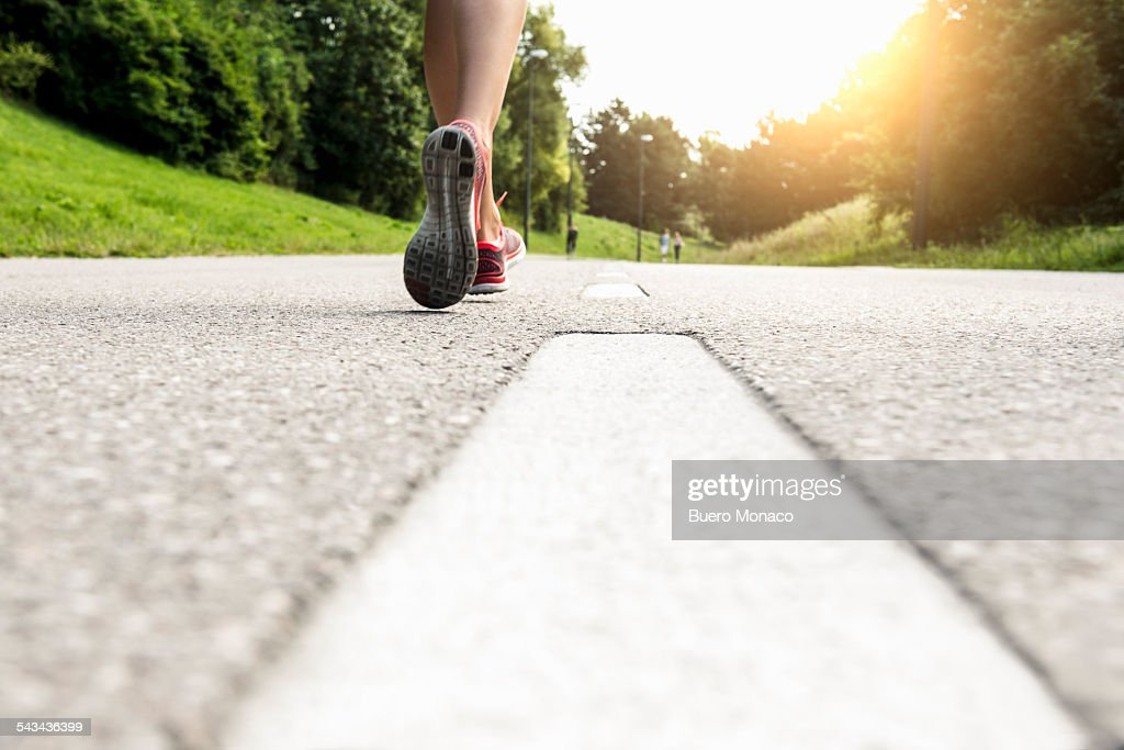 close up of female runners feet on street with sun