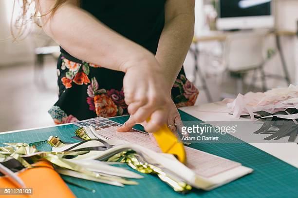 Close up of female textile designer cutting textiles in design studio