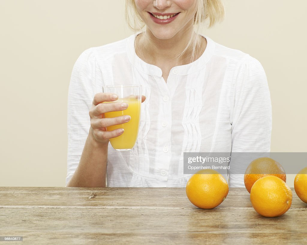 close up of female with glass of orange juice : Stock Photo