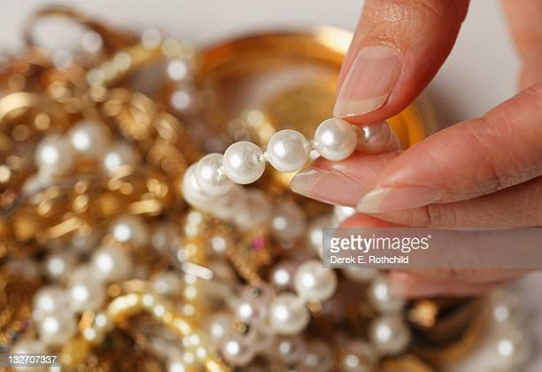 Close up of fingers and pearls