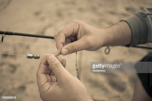 Close up of fishermans hands preparing fishing rod, Truro, Massachusetts, Cape Cod, USA