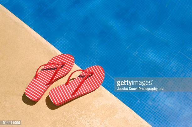 Close up of flip flops by swimming pool
