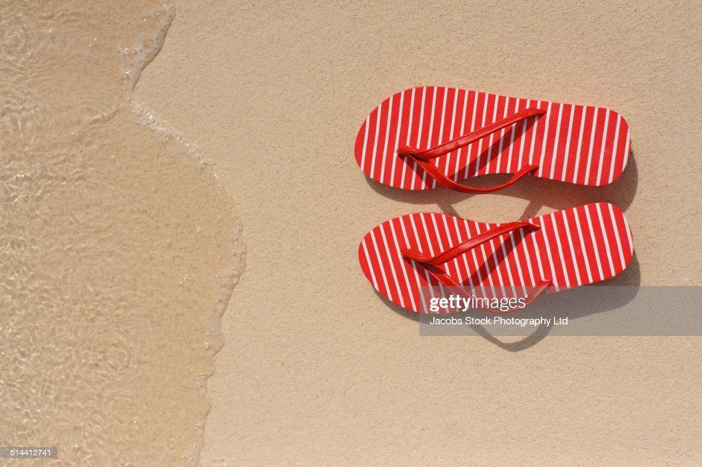 Close up of flip flops on beach