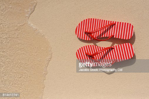 Close up of flip flops on beach