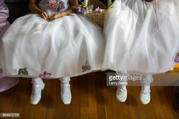 Close up of flower girls dresses, socks and white shoes