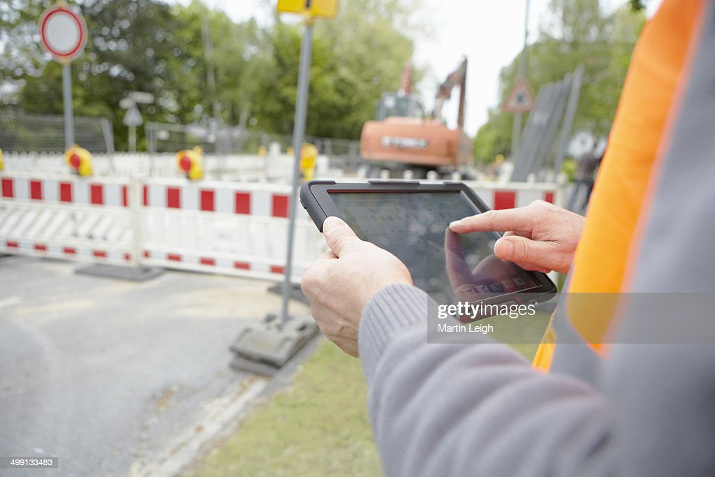 Close up of foremans hands using digital tablet on road construction site